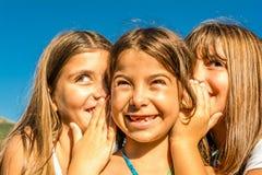 Drei sieben jährige spielende und flüsternde Mädchen Lizenzfreies Stockbild