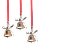 Drei silberne Glocken auf roten Bändern Stockfotografie