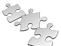 Drei silberne Puzzlespiele, die fliegen, um zu lüften Lizenzfreies Stockbild