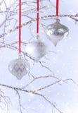 Drei silberne Weihnachtsverzierungen mit Schnee Stockfotografie