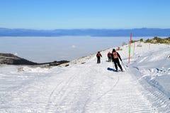 Drei Skifahrer steigen von der Spitze ab Stockfotografie