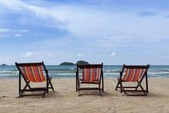 Drei Sonnenstühle auf dem Strand Stockfotografie