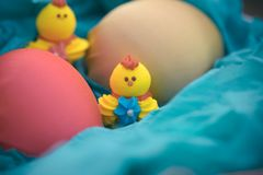 Drei Spielzeughühner und drei Ostereier auf dem Gras in einem blauen Korb Lizenzfreie Stockfotos