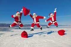 Drei springende Santa Claus draußen Stockbilder