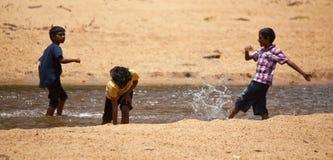 Drei Sri Lankan Jungen, die in einem Strom spielen Lizenzfreie Stockbilder