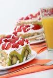 Drei Stücke des selbst gemachten Kuchens wird mit Orangensaft gedient Stockbild