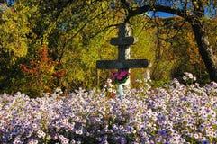 Drei-Stab orthodoxes Kreuz unter Blumen Stockfotografie