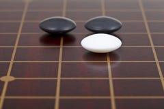 Drei Steine während gehen das Spiel, das auf goban spielt Lizenzfreies Stockfoto
