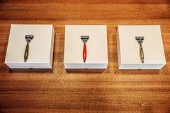 Drei stilvolle Rasiermesser mit Kästen auf dem Holztisch lizenzfreies stockfoto