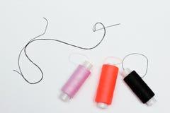 Drei Stränge mit Threads und einer Nähnadel Stockfotos