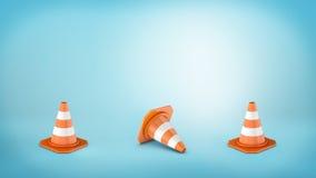 Drei streiften die Verkehrskegel, die auf blauen Hintergrund gesetzt wurden und das mittlere, das auf seine Seite liegt Lizenzfreie Stockbilder