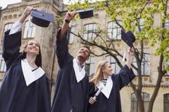 Drei Studenten, die an ihrem Graduierungstag lachen Stockfotos
