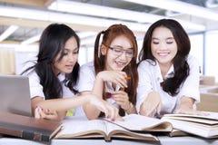 Drei Studenten lasen Bücher zusammen in der Klasse Stockfotos