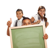 Drei Studenten mit den Daumen, die leeres Kreide-Brett auf Weiß hochhalten Lizenzfreie Stockfotos