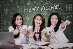 Drei Studentinnen, die sich Daumen zeigen Stockbilder
