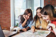 Drei Studentinnen, die zusammen Geografiehausarbeit zu Hause tun stockfotografie