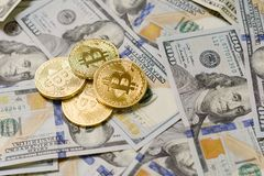 Drei symbolische Münzen bitcoin auf Banknoten von hundert Dollar Austausch bitcoin Bargeld für einen Dollar Lizenzfreies Stockfoto