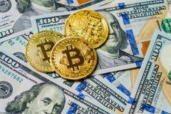 Drei symbolische Münzen bitcoin auf Banknoten von hundert Dollar Austausch bitcoin Bargeld für einen Dollar Lizenzfreie Stockfotos