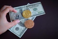 Drei symbolische Münzen bitcoin auf Banknoten von hundert Puppe Lizenzfreie Stockbilder