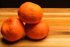 Drei Tangerinen auf Teakholz-Schneidebrett Lizenzfreie Stockfotografie