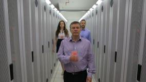 Drei Techniker, die hinunter die Halle gehen stock video