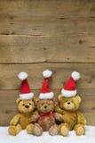 Drei Teddybären mit Weihnachtshüten auf hölzernem Hintergrund Stockbild