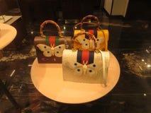 Drei teuer, moderne, stilvolle, schöne Taschen mit Schmetterlingen in einem Shopfenster Stockbild