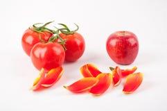 Drei Tomaten und ein Apfel Stockbild