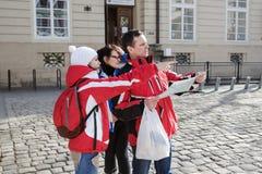 Drei Touristen betrachten die Karte der Stadt ` s Anziehungskräfte stockfotos