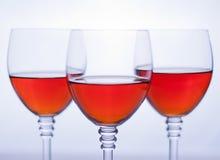 Drei transparente Weingläser mit rosafarbenem Wein. Lizenzfreie Stockfotografie