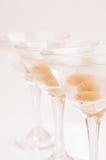 Drei trockene Martini-Cocktails schließen oben über hellpurpurnem Hintergrund Stockfotografie