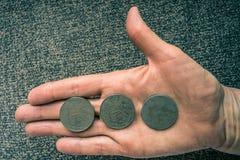 Drei tunesische Münzen auf dem woman& x27; s-Palme Lizenzfreie Stockfotos