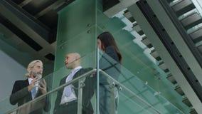 Drei Unternehmensgeschäftsleute, die im modernen Bürogebäude stehen und sprechen