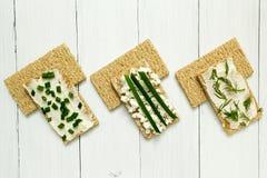 Drei vegetarische Fr?hst?cke, Toast, H?ttenk?se, Zwiebeln und Dill auf einem wei?en Holztisch, Di?t stockbilder