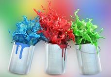 Drei verschiedene Farben, die von den Farbeimern spritzen Stockfoto