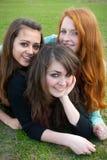 Drei verschiedene Mädchen sitzen auf dem Gras und Lizenzfreies Stockbild