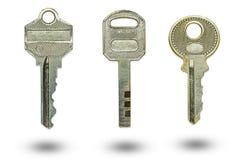 Drei verschiedene Schlüssel auf einem weißen Hintergrund stockfotografie