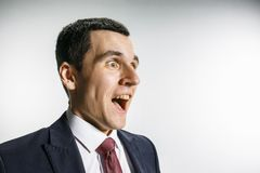 Drei-Viertelporträt eines Geschäftsmannes mit überraschtem und lächelndem Gesicht Überzeugter Fachmann mit Durchdringenblick here lizenzfreie stockfotos