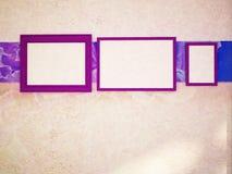 Drei violette Rahmen auf der Wand, Stockfotografie