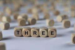 Drei - Würfel mit Buchstaben, Zeichen mit hölzernen Würfeln stockfotos