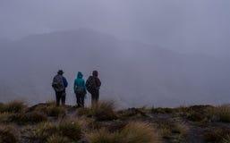 Drei Wanderer, die Bergspitzen-Wolken aufpassen Stockbild