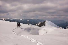 Drei Wanderer, die hinunter eine Schritthügelklippe zum Dorf nach langer Bergwanderung in der Winterschneekälte gehen Stockbild