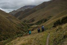 Drei Wanderer, die zur Gebirgshütte absteigen Lizenzfreie Stockfotografie