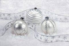 Drei weiß und silberne Weihnachtsverzierungen auf Schnee Stockfotos