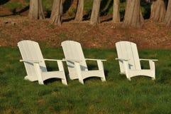 Drei weiße adirondack Stühle auf einem Gebiet Stockbilder