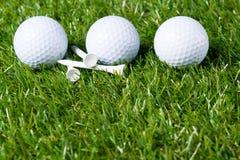 Drei weiße Bälle liegen auf einem Rasen für das Spielen des Golfs als Hintergrund stockbild