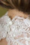Drei weiße glatte Knöpfe auf Spitzehochzeitskleid Stockfoto