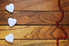 Drei weiße Herzen falsch ausgerichtet und hölzerner Hintergrund mit Halskette stockfotografie