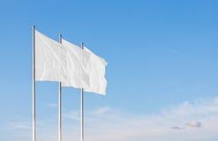 Drei weiße leere Unternehmensflaggen, die in den Wind wellenartig bewegen Stockbilder