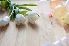 Drei weiße Tulpen und kleine Ballone auf einem hölzernen Hintergrund Stockbild